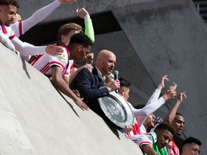 Ajax coach Erik ten Hag and players hold the trophy as they celebrate clinching the Dutch Eredivisie Premier League title at the Johan Cruyff ArenA in Amsterdam, Netherlands