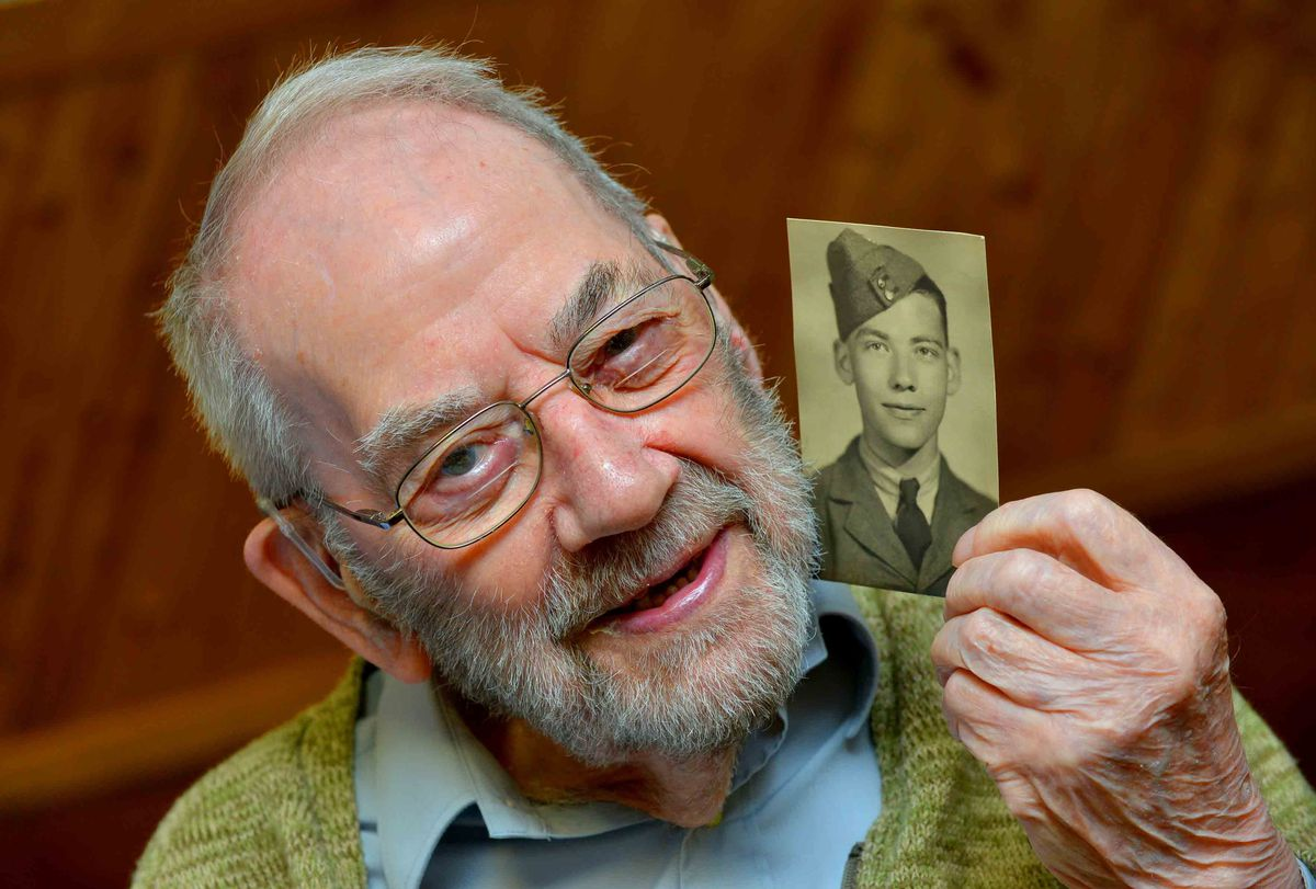 Roy Tomlin with a photograph of himself in in his RAF days
