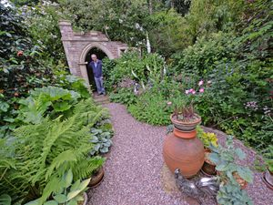Brian Bailey in the folly, one of the unique parts of the garden