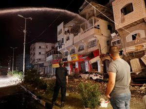 Firefighters extinguish burning apartment buildings after they were hit by Israeli airstrikes, in Gaza City