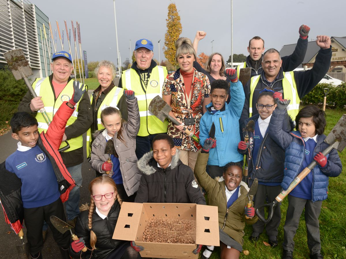 Gerald Brooks, President of Bilston Rotary Club and Councillor Beverley Momenabadi, centre, with children from Bilston CofE Primary School as they plant crocuses