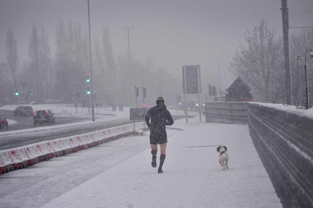 A lone jogger - and his dog - braves the weather as he runs in Cannock