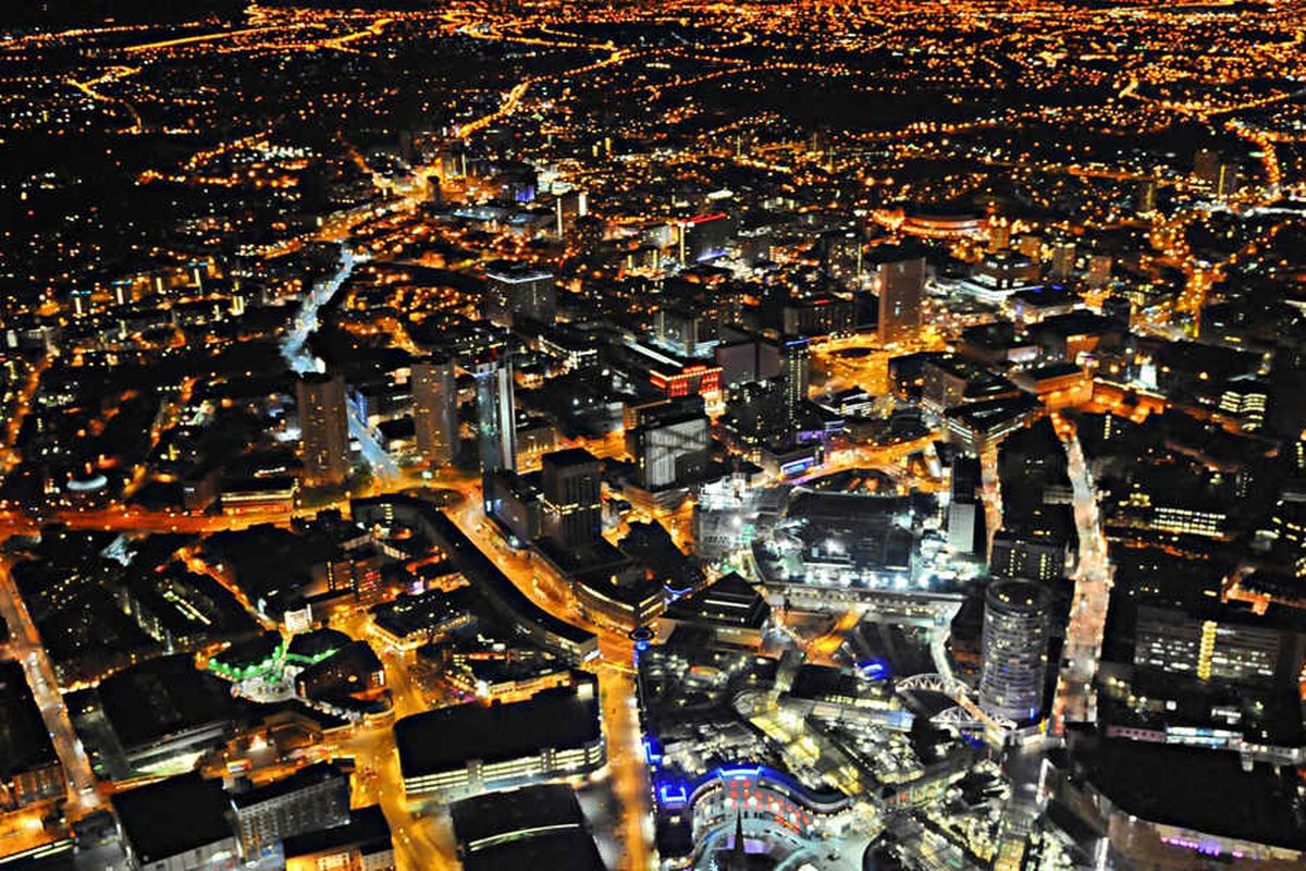 Birmingham city centre is captured by the police helicopter at night with the landmark Rotunda, right, The Mailbox, centre, while the ICC and NIA are at the top right