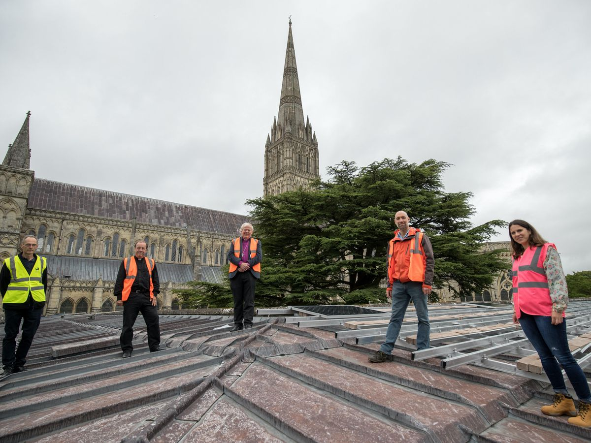 From left to right, James Page of Joju Solar, Robert Titley, Canon treasurer of Salisbury Cathedral, the Rt Rev Nicholas Holtam, Bishop of Salisbury, Thomas Burnett, a Director of Salisbury Community Energy and Laura Moreno of Joju solar, on the roof of Salisbury cathedral's south cloister