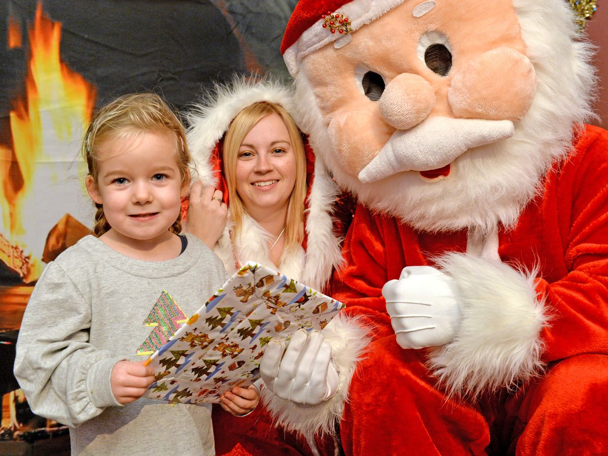 Children visiting the Landywood school Santa's grotto outside. Pictured left with Santa are Amelia Belsy age three and Charlie Titley