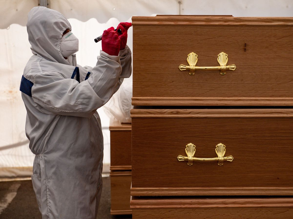 A volunteer marks coffins at Central Jamia Mosque Ghamkol Sharif in Birmingham in April 2020, which operated as a temporary morgue during the Covid-19 pandemic