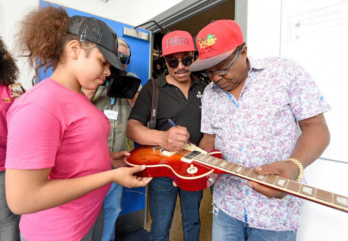 Marlon and Tito sign a guitar for Kamara Brown from Bentley Bridge