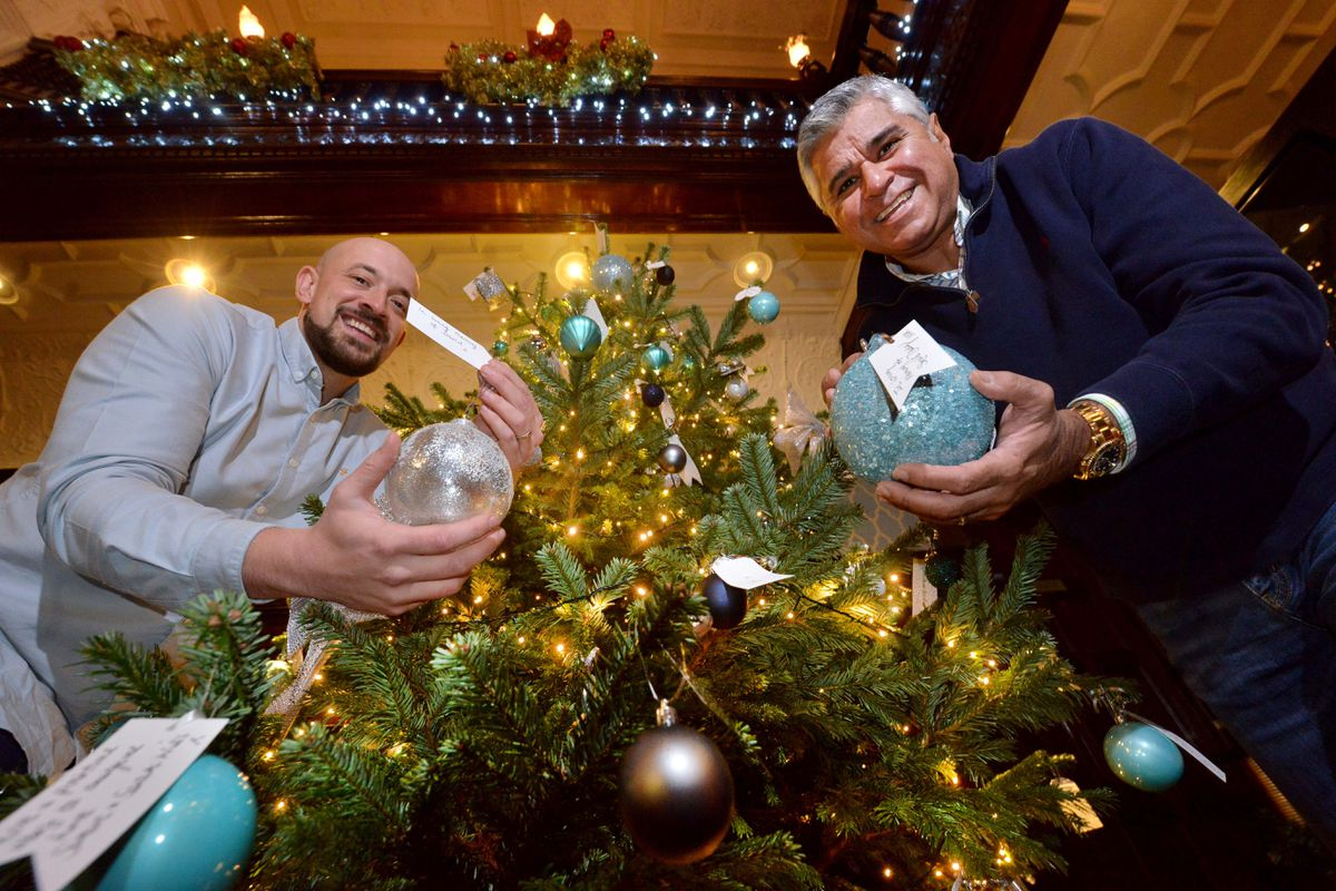 Hotel managing director Scott Bernard (left) with Promise Dreams trustee Suresh Bawa next to the Christmas tree where the baubles have been placed.