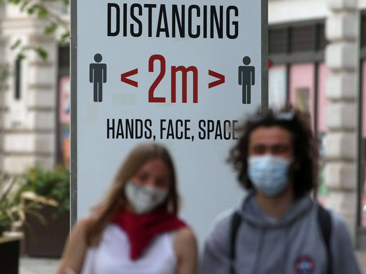 Two people wearing masks in front of a social distancing sign in Regent Street, London