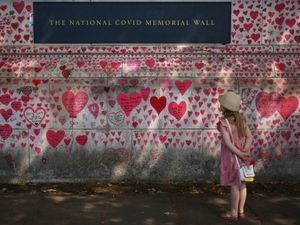 A child looks at the National Covid Memorial Wall in London