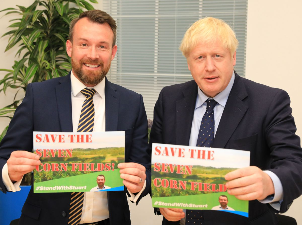 Stuart Anderson, left, with Boris Johnson, right, holding placards saying 'Save the Cornfields!'