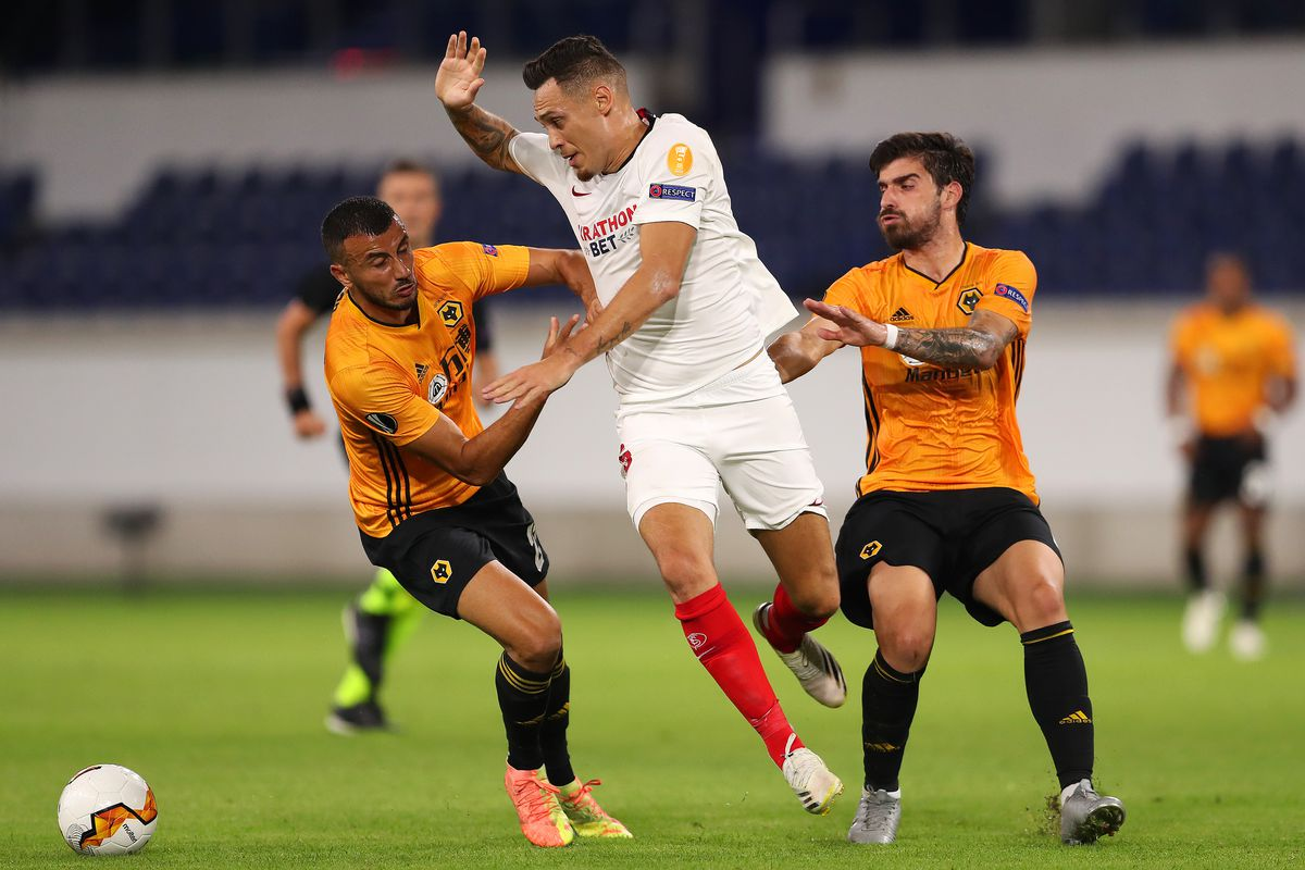 Ruben Vinagre and Ruben Neves of Wolverhampton Wanderers compete with Lucas Ocampos of Seville (AMA)