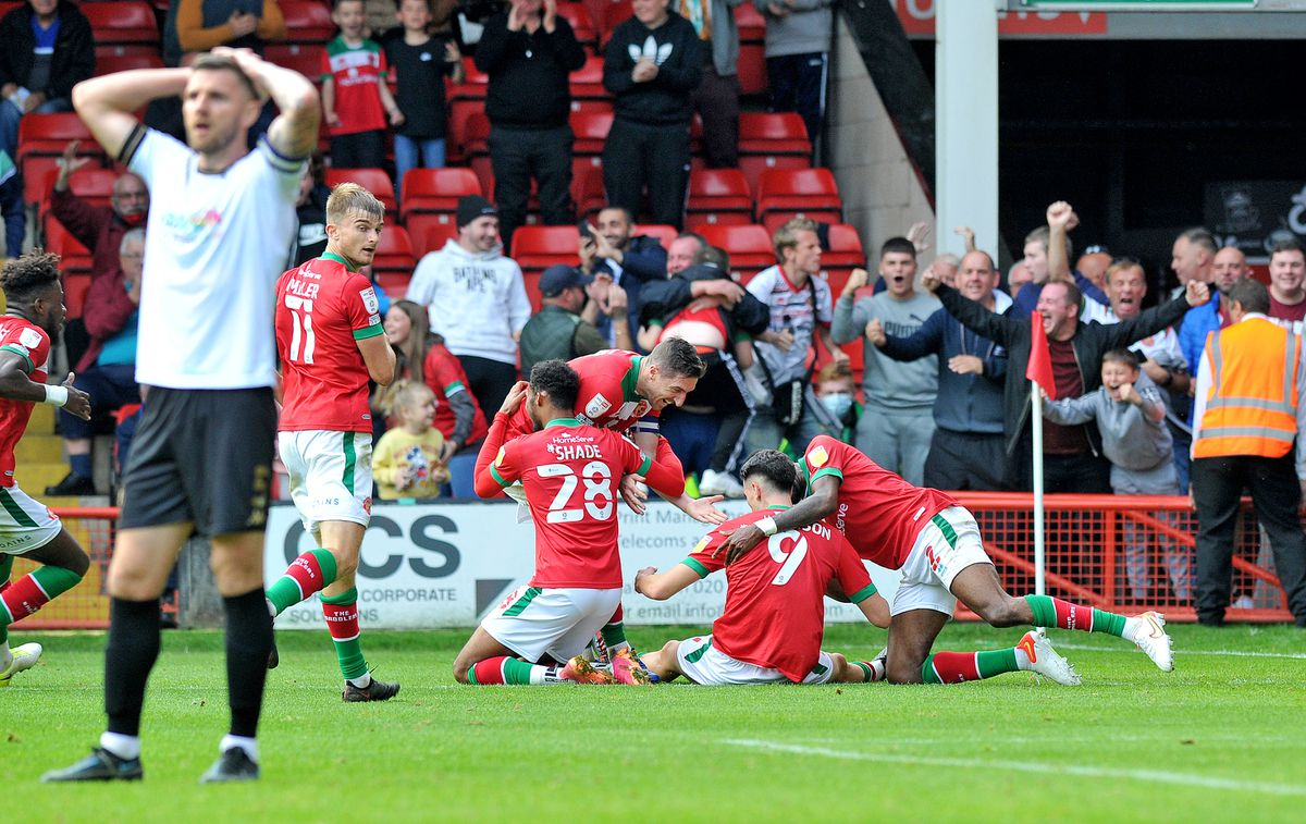 Players mob Conor Wilkinson after he scores the winner.
