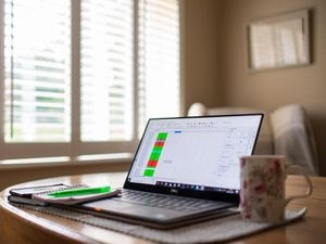 A laptop on a dining room table set up as a remote office to work from home