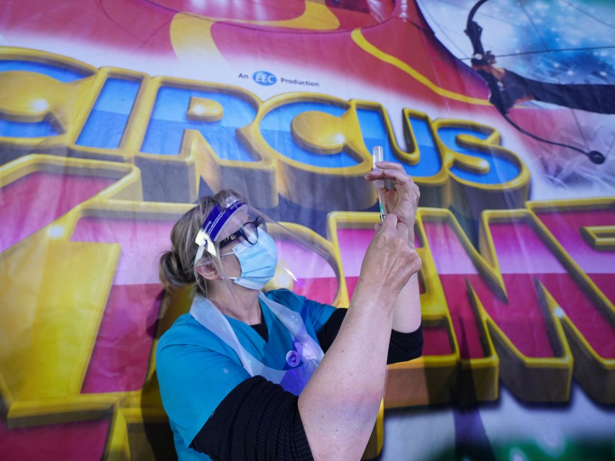 Dr Lisa Pickles, 57, clinical lead for the Calderdale vaccination program prepares a syringe at a pop-up Covid-19 vaccination clinic in the marquee of Circus Extreme in Halifax (Owen Humphreys/PA)