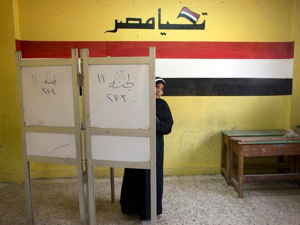 A woman prepares to vote during the second day of the presidential election at a polling station in Cairo