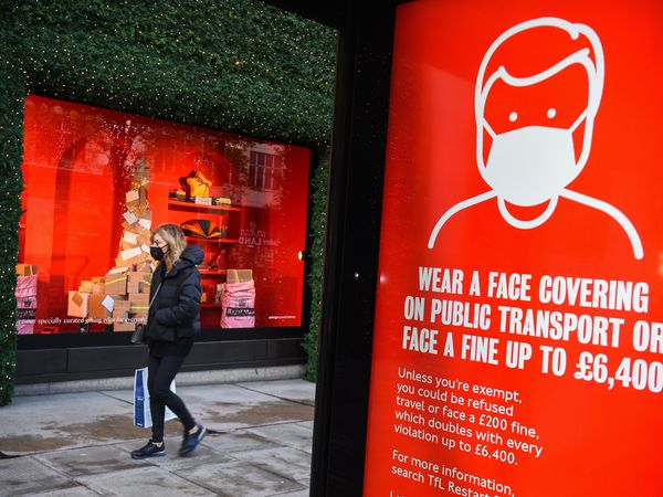 A woman wearing a face mask passes a screen advising the wearing of face masks on Oxford Street, London