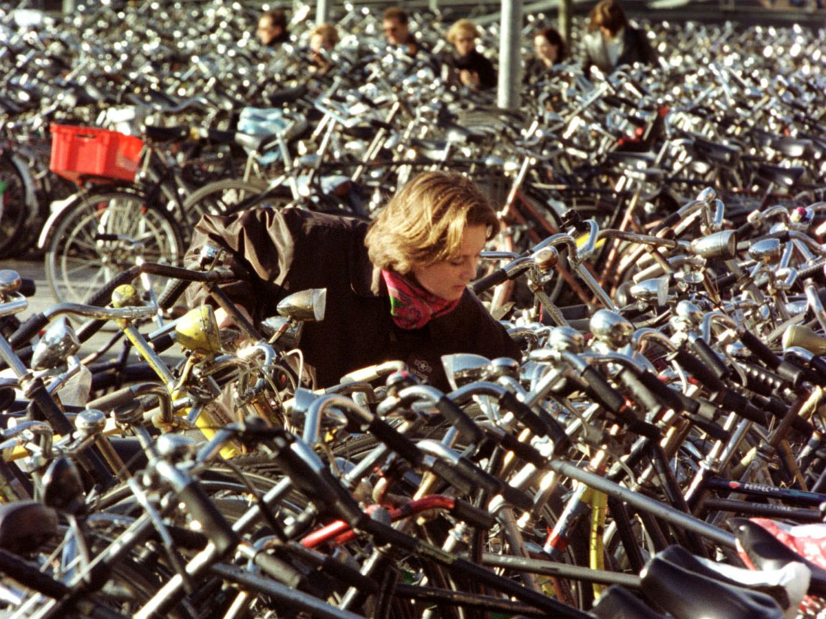 A girl unlocks her bicycle parked amidst thousands of others at Amsterdam's Central Station