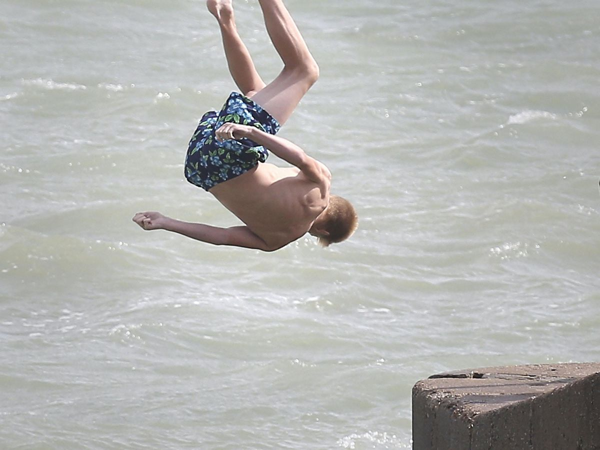 A boy jumps into the sea from a jetty on Dover sea front.
