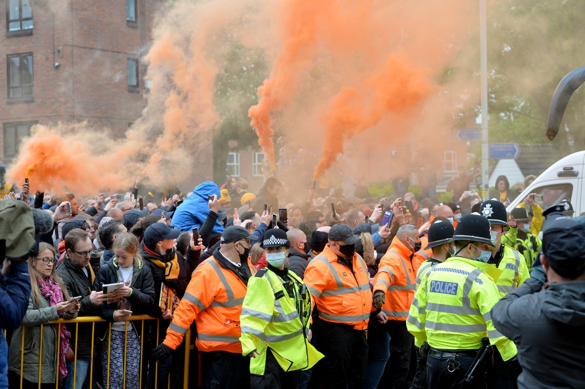 Fans celebrate as the Wolves coaches turn up at Molineux on Sunday