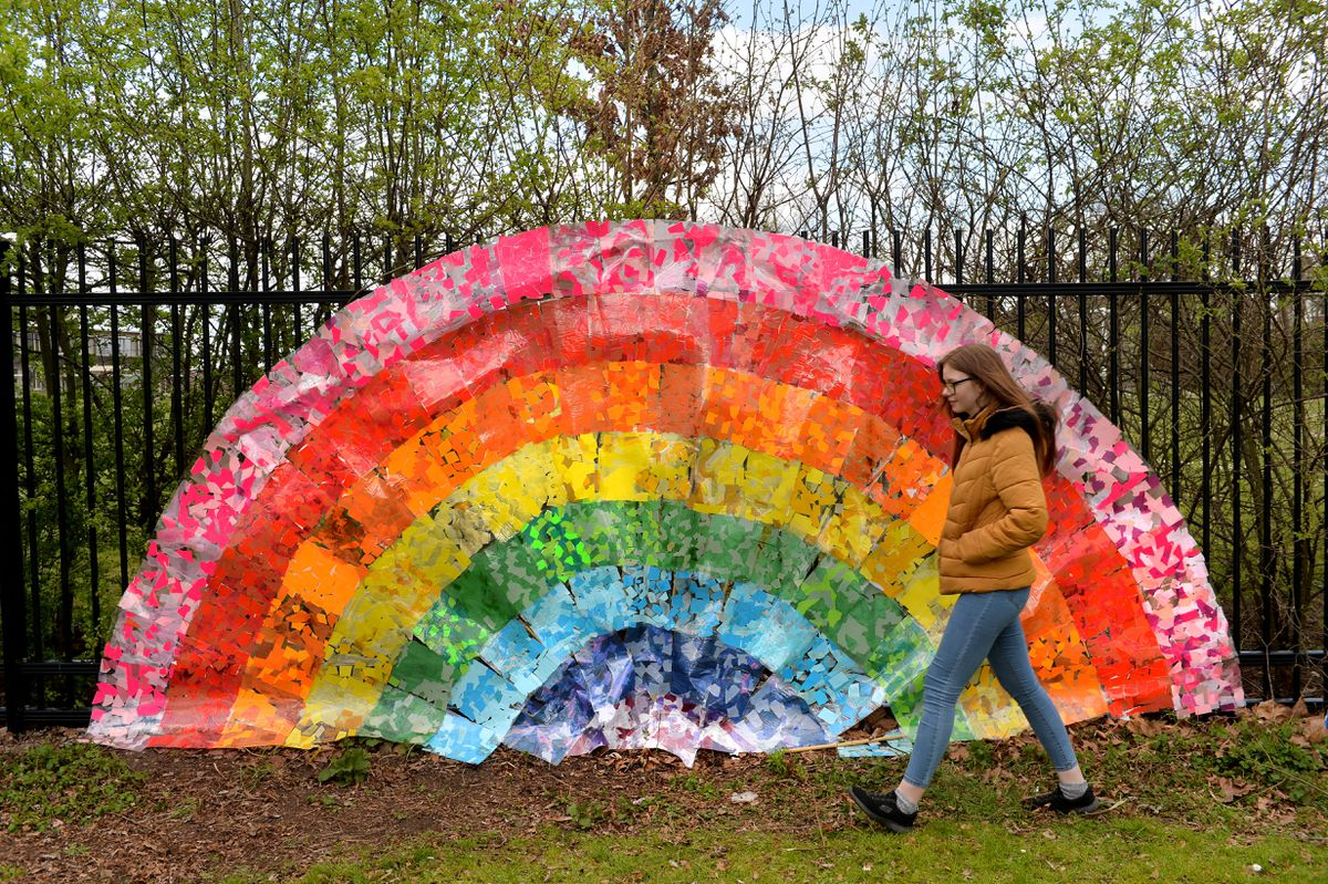 Casey Goode walks past a giant rainbow on the fence of Oak Meadow Primary School, in Ashmore Park, Wolverhampton