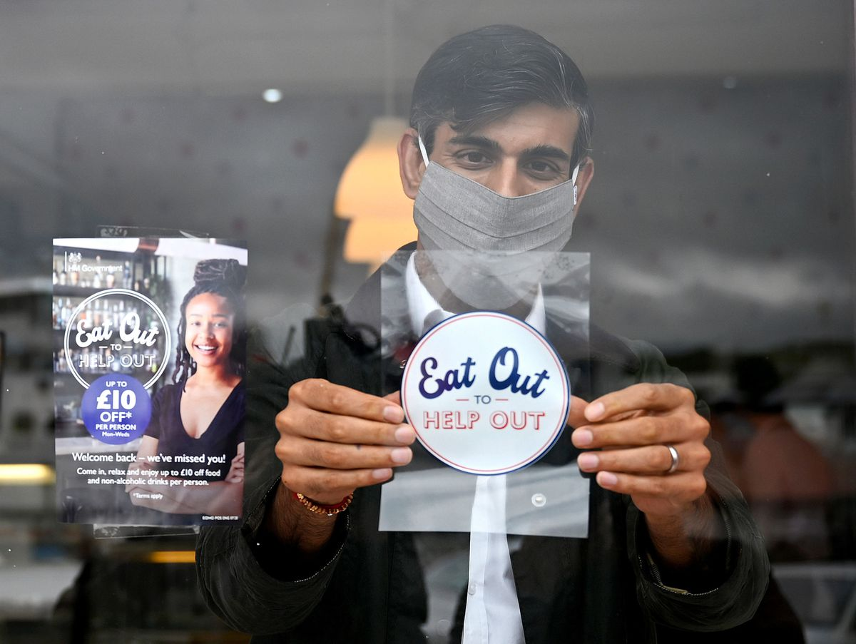 Chancellor Rishi Sunak places an Eat Out to Help Out sticker in the window of a business