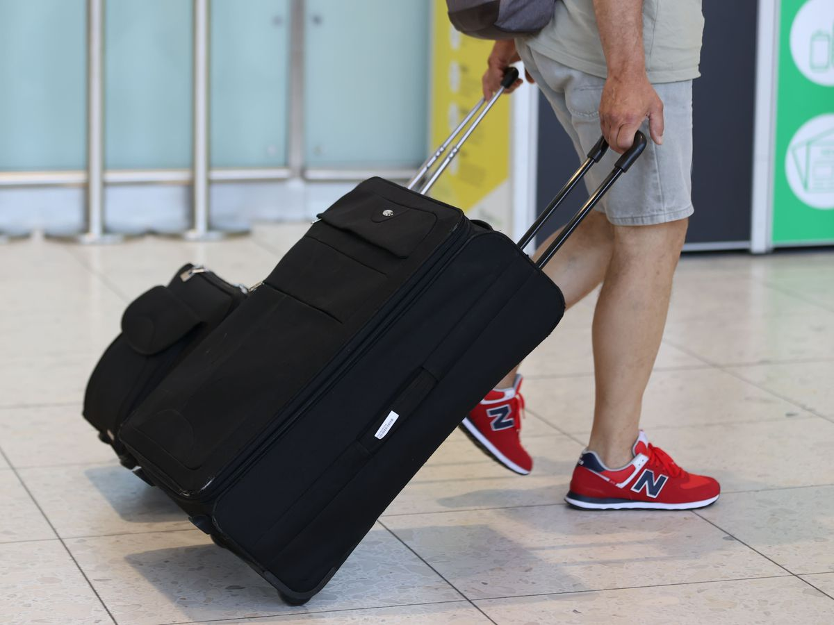 An airline passenger pulls a suitcase in an airport