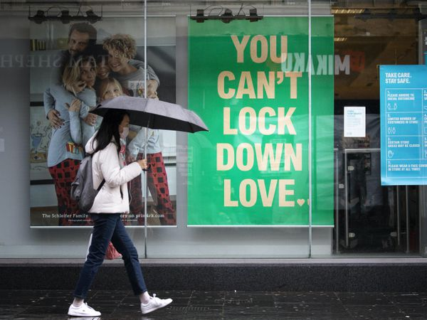 A woman walks past a shop sign that reads 'you can't lock down love'
