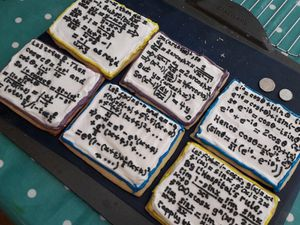 A photo of several biscuits with complicated maths piped on top