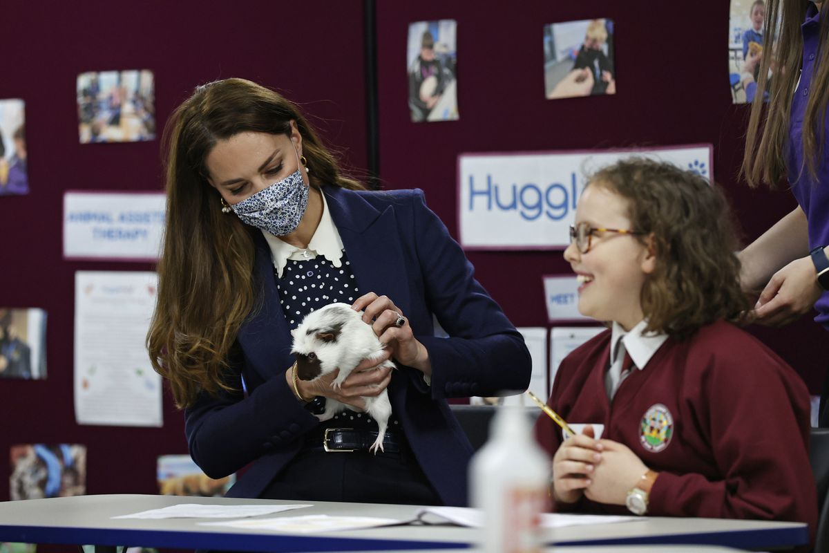 The Duchess of Cambridge handles Gus the guinea pig alongside children from Loxdale Primary School during a visit to HugglePets in the Community in Wolverhampton