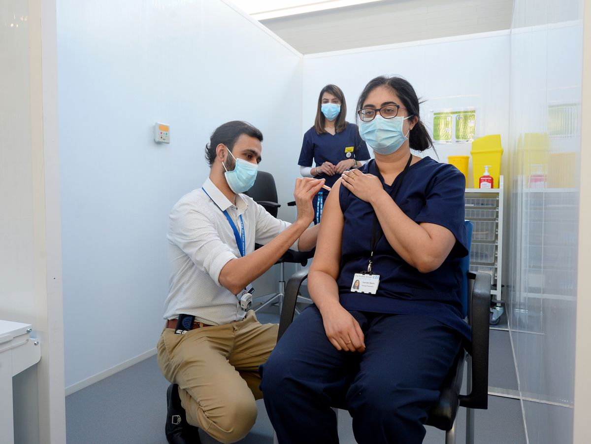 Pharmacist Davinder Manku is the first person to get the vaccination at the museum from fellow pharmacist Syed Anas Gilani