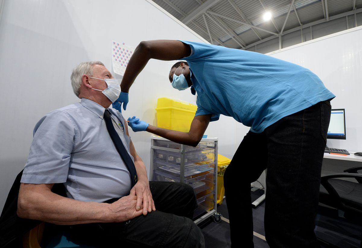 Neil Burgess from Willenhall, gets the jab from assistant practitioner Opeyemi Ajulo