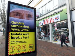 A person walks past a Government coronavirus poster