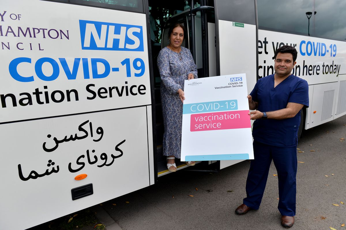 Councillor Jasbir Jaspal and Dr Raj Mohindroo outside the mobile vaccine bus in Blakenhall