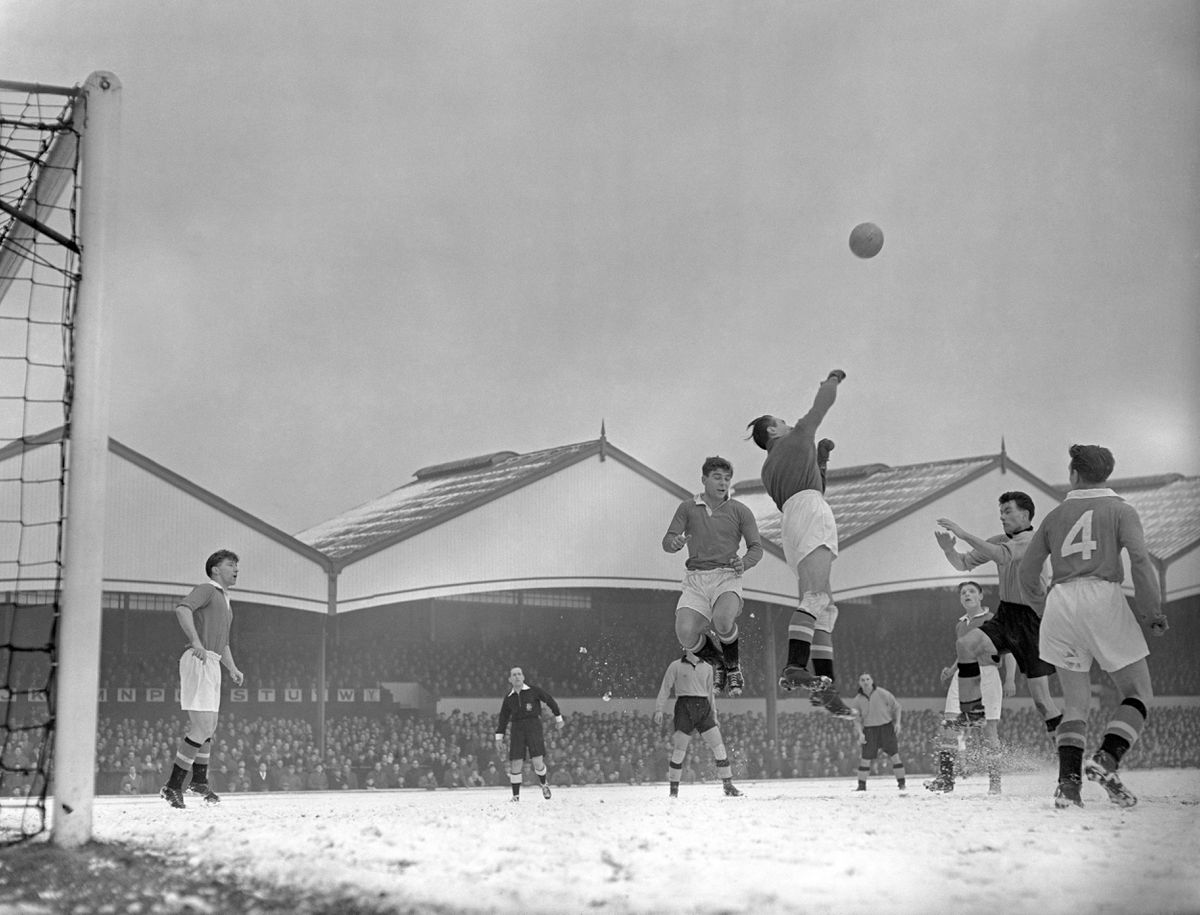 Duncan Edwards, jumping high, centre, during a game against Wolves