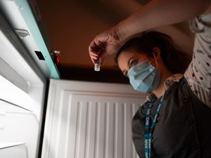 Pharmacist Ciara Duffy removes Pfizer BioNTech Covid-19 vaccines from a fridge
