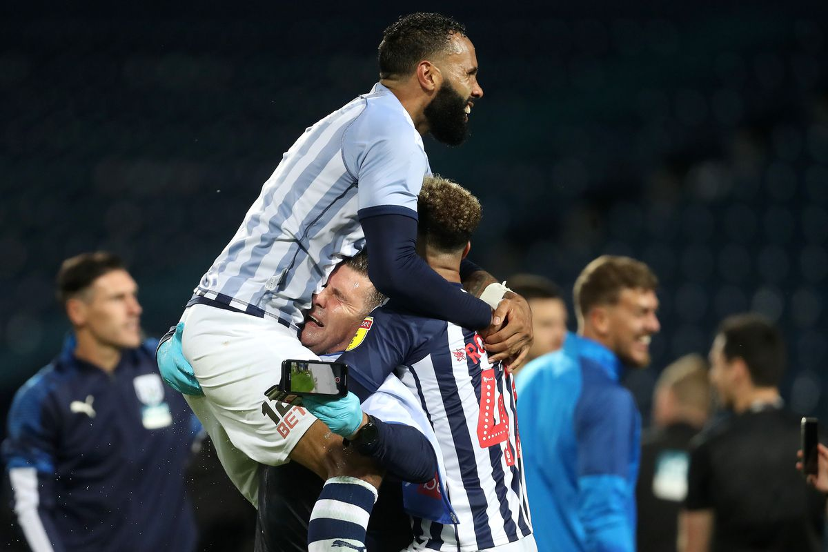 Kyle Bartley of West Bromwich Albion and Callum Robinson of West Bromwich Albion  embrace as they celebrate promotion to the Premier League on the pitch at the end of the match. (AMA)
