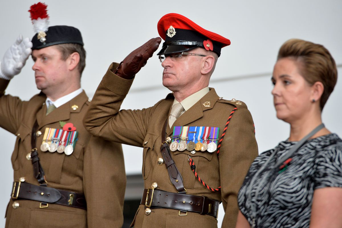 Servicemen and staff pay their respects during the service at Walsall College