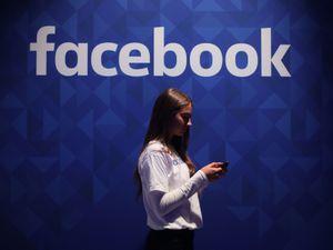 Woman stands under Facebook logo