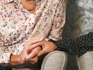 """EMBARGOED TO 0001 SATURDAY SEPTEMBER 4..File photo dated 04/09/21 of a care home resident holding hands with her daughter. The Government is being warned of widespread closures of care homes unless it scraps the """"no jab, no job"""" law in England. Issue date: Saturday September 4, 2021. PA Photo. The union said the controversial mandatory vaccination rule for England was pushing thousands of workers to the brink of quitting care work ahead of the September 16 deadline to get their first vaccination or face losing their job. See PA story INDUSTRY Care. Photo credit should read: Andrew Matthews/PA Wire ....."""