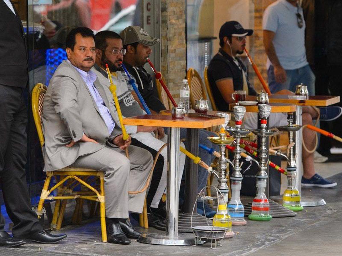 General view of customers smoking shisha pipes outside a cafe (Dominic Lipinski/PA)