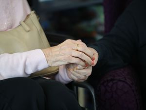 An elderly care home resident holds hands with a visitor