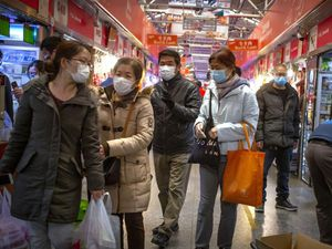 People wear face masks as they shop at a market in Beijing