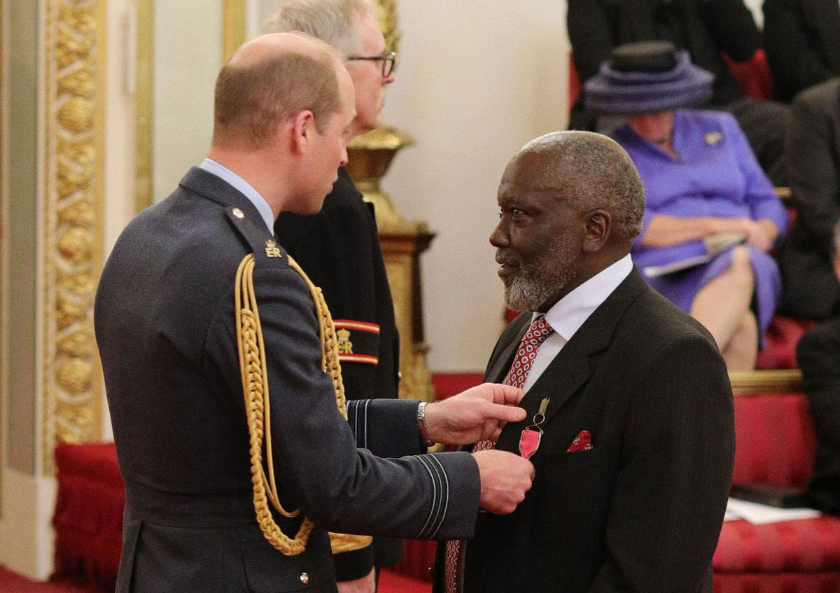 Dr Johnson receiving his MBE from Prince William