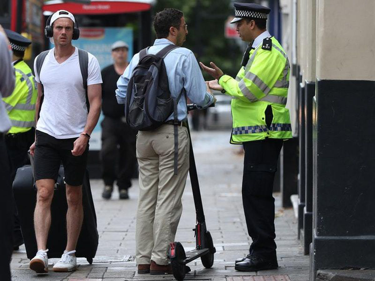 An e-scooter rider is stopped by police in north London (Yui Mok/PA)