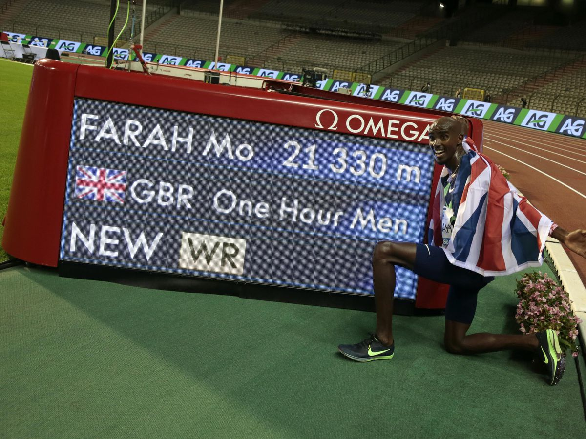 Sir Mo Farah poses next to the board after setting a world record (