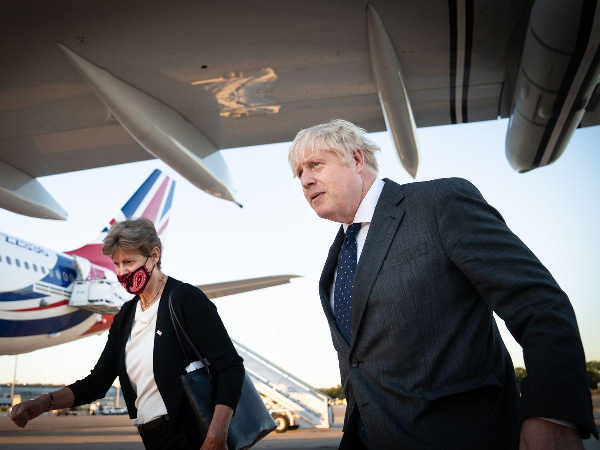Boris Johnson, accompanied by Dame Barbara Janet Woodward walks across the tarmac of New York's JFK airport