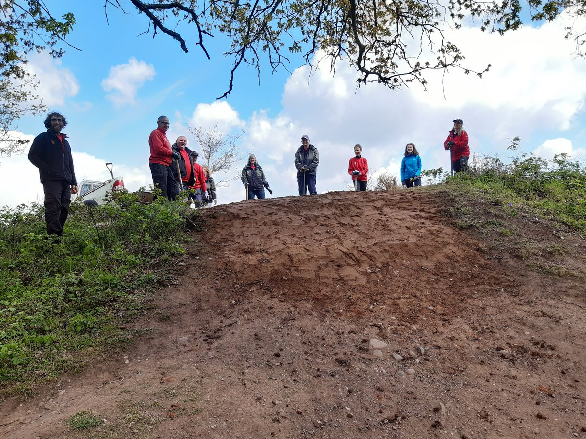 Volunteers and rangers pose as they continue the repair work to the hilltop fort