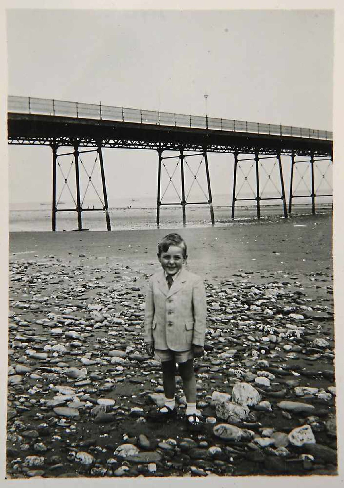 A young, smartly-dressed Eric on a beach in the 1940s