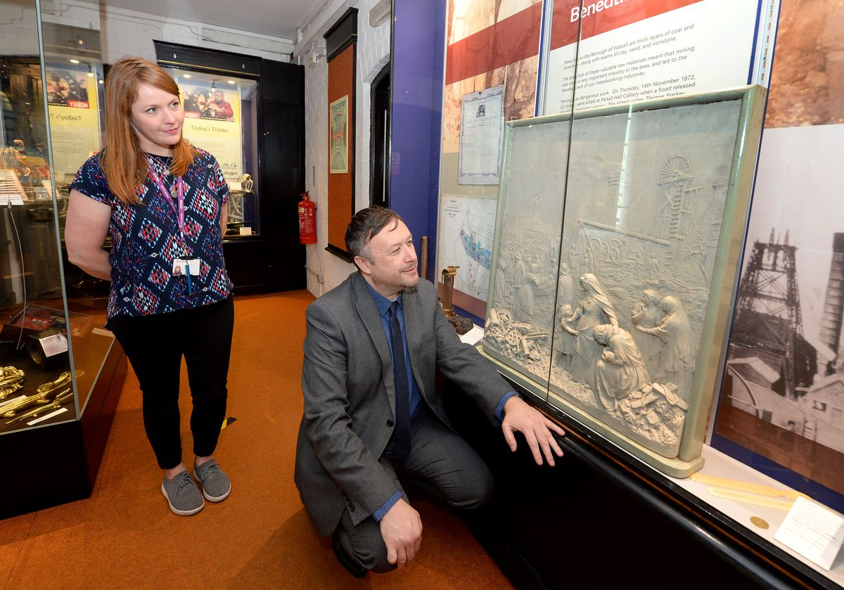 Councillor Garry Perry and collections officer Catherine Lister view one of four casts of bronze reliefs, that decorate the base of the Sister Dora statue